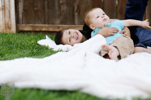 two brothers hugging on a blanket in the backyard