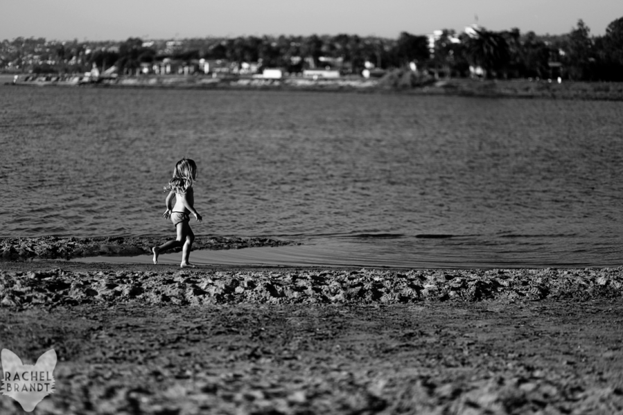 Girl runs along the shore in San Diego