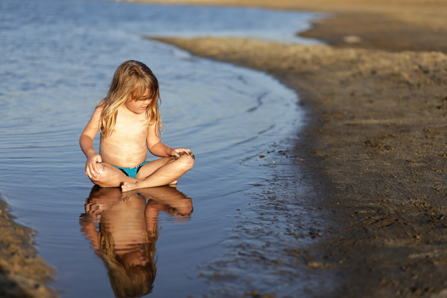 LIttle girl and her reflection in the Pacific Ocean